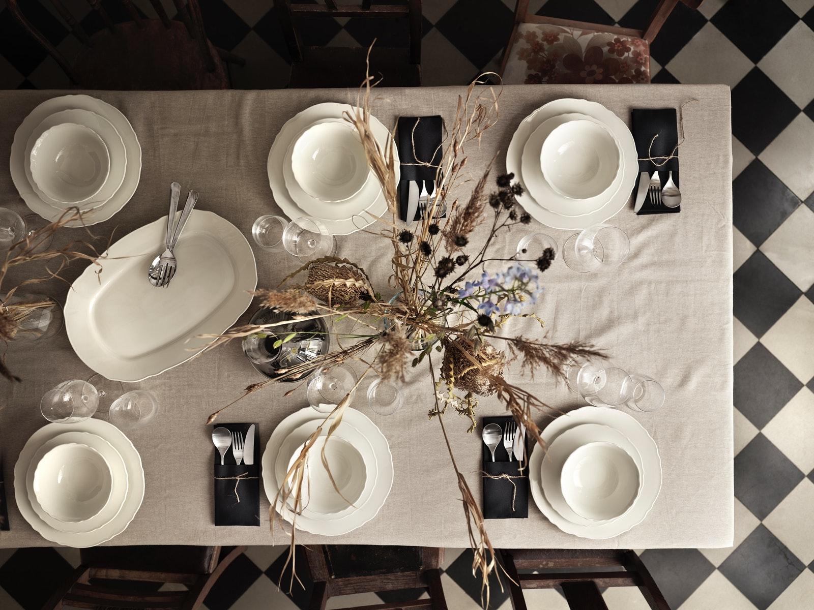 UPPLAGA瓷器系列的白瓷碗碟及杯放在木檯面上。