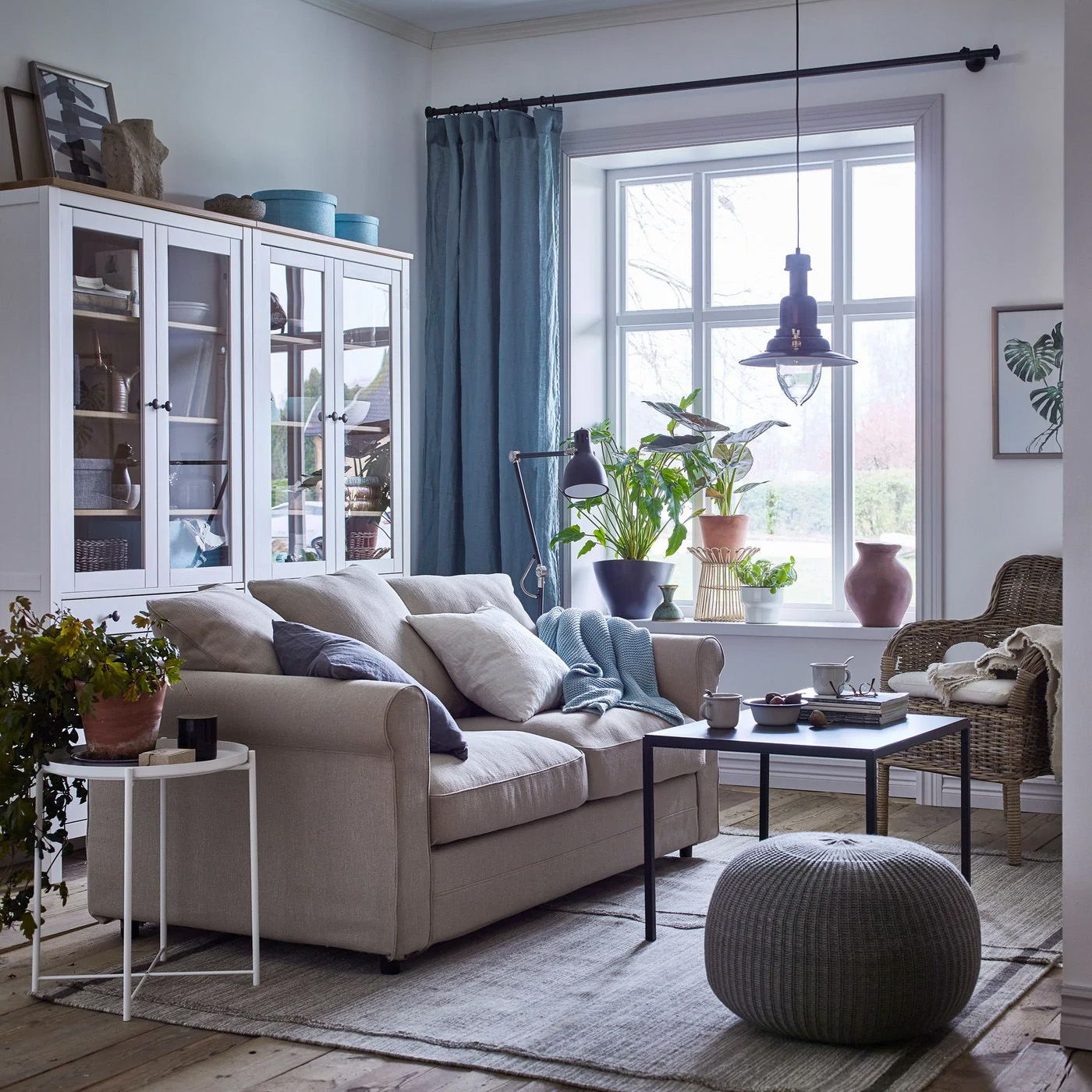 A cosy beige and white living room with blue curtains and a GRÖNLID 2 seat sofa in sporda natural beside a rattan chair and glass door cabinet.