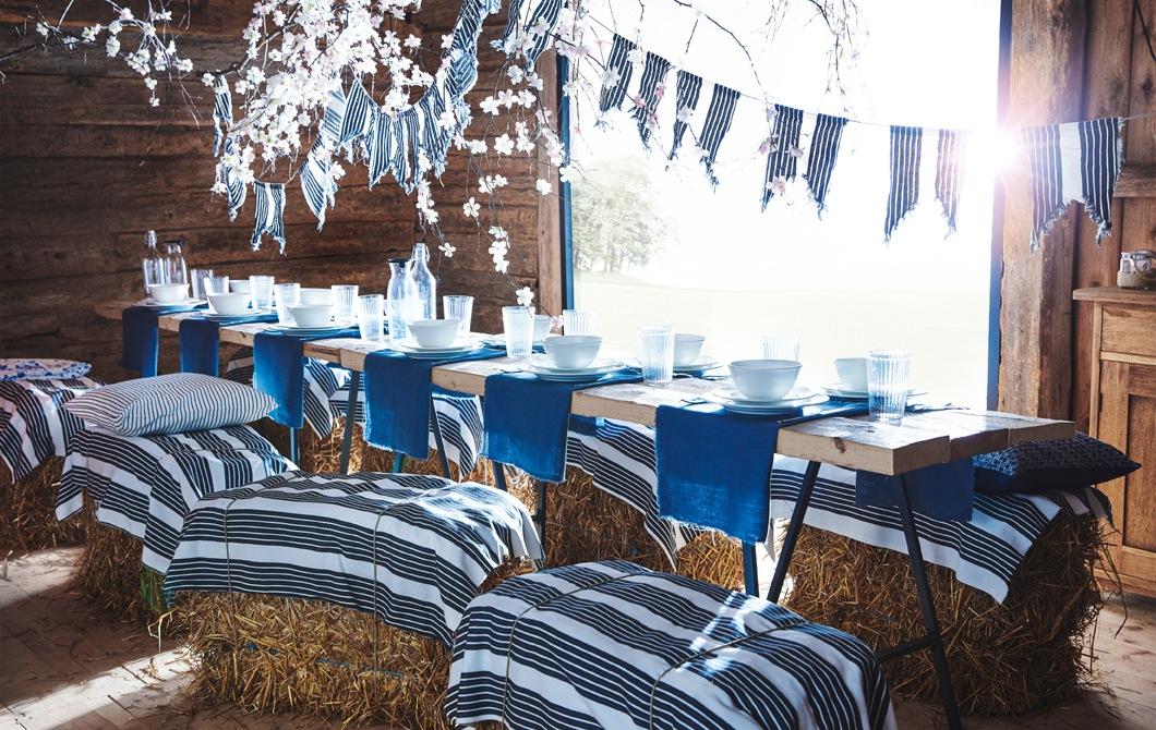 木造穀倉內的長檯上放有藍白色餐具,而條紋布則製成彩旗,並綁在用作座椅的乾草堆上。