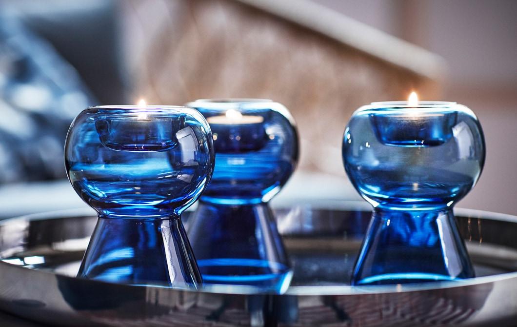 放在銀色托盤上的三個藍色玻璃燭台