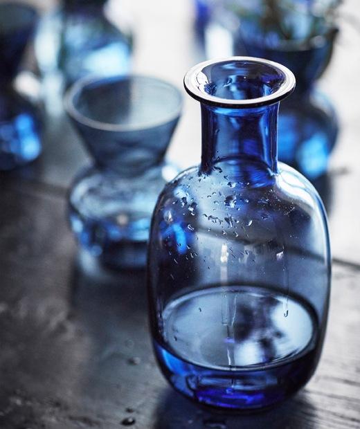 放在深色木檯上的藍色玻璃水瓶及藍色小花瓶。