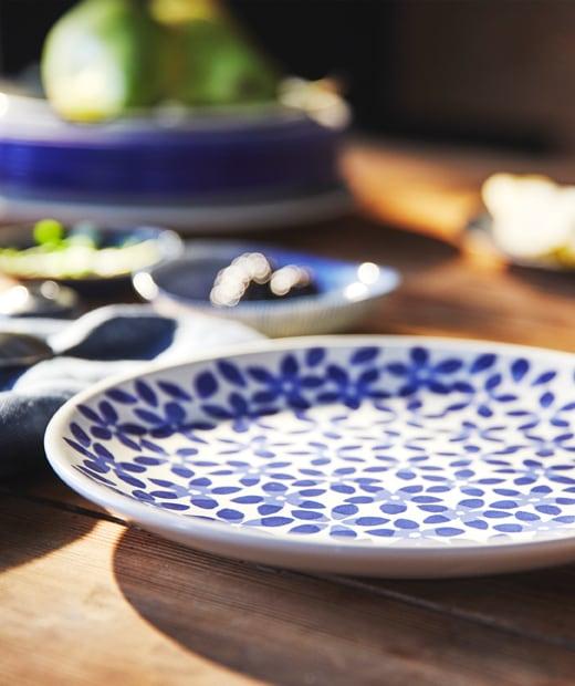 放在木檯上的藍白色繪花圖案餐碟,旁邊還有一疊碟。