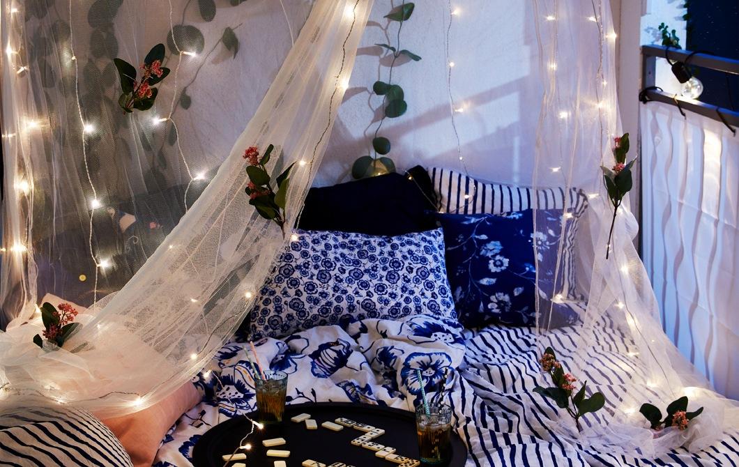 有門露台放著一張寬闊大床,蚊帳綴以人造花及LED燈串,托盤上有些飲品及遊戲。