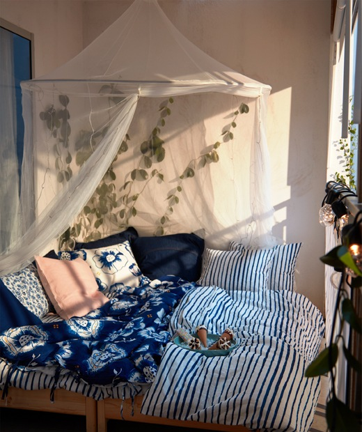 Sunlit balcony with double bed softly piled with cushions and blue-white bedlinen; mosquito net above, plants around.