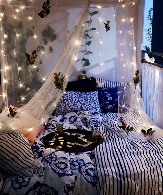 Night-time balcony setting of a double bed, a tray with drinks resting on it, and a net with lighting chains hanging above.