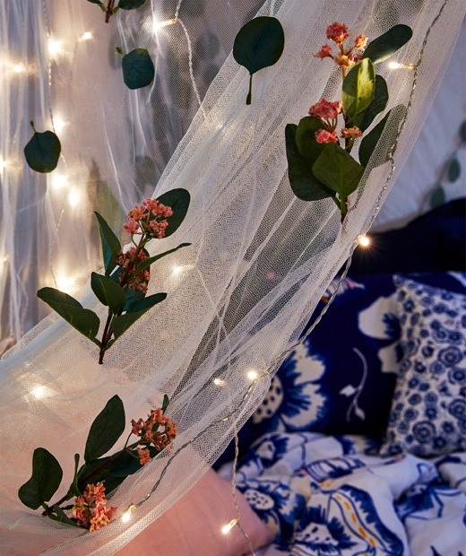 Section of mosquito net draped over a bed at night, the net decorated with artificial flowers and multiple lighting chains.