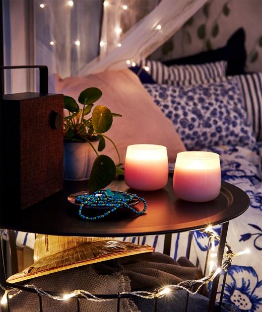 露台布置,背後有一張床,前方有一張小圓檯,上面有ENEBY 藍芽擴音器及燃點著的香味蠟燭。