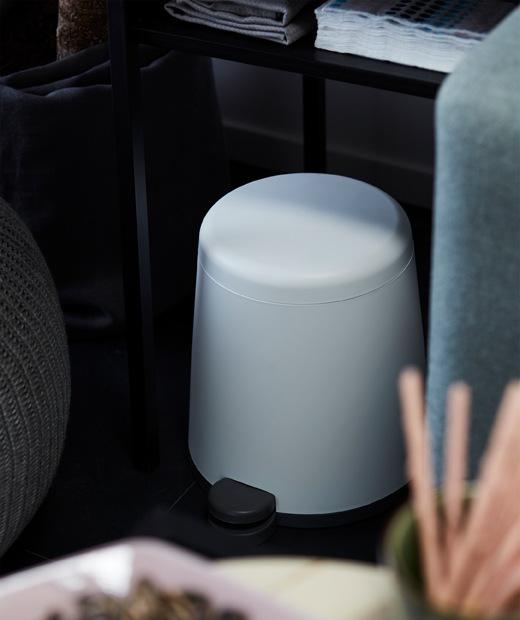 SNÄPP腳踏式垃圾桶採用圓角筒形設計,半邊放在客廳梳化與地板坐墊之間的茶几下。