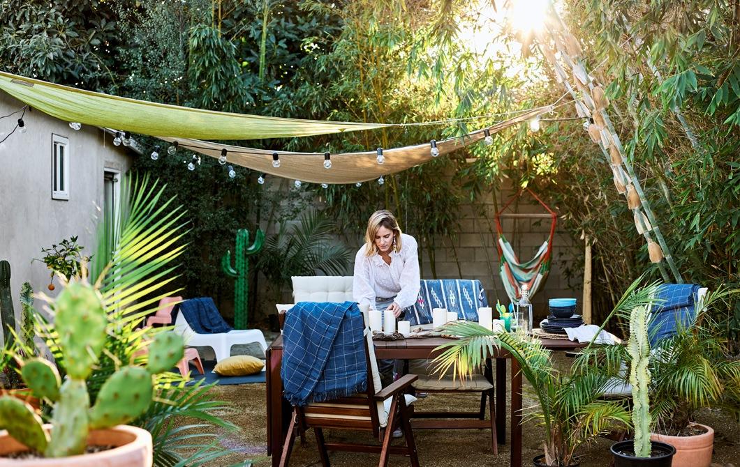 Chloé在花園布置餐檯,花園內有木傢具、盆栽、樹、頂篷和裝飾燈串。