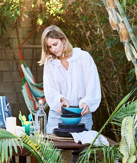 Chloé在花園的木檯上把碗疊起。