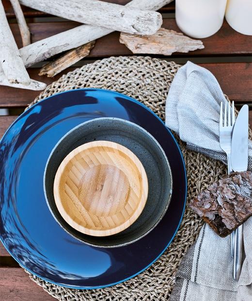 木檯上的編織檯墊上有一疊深藍色和木碗,還有浮木。