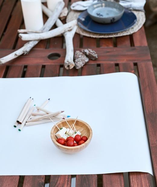 木檯上有白紙、顏色筆和一小碗零食,旁邊是浮木和已放好的餐具。