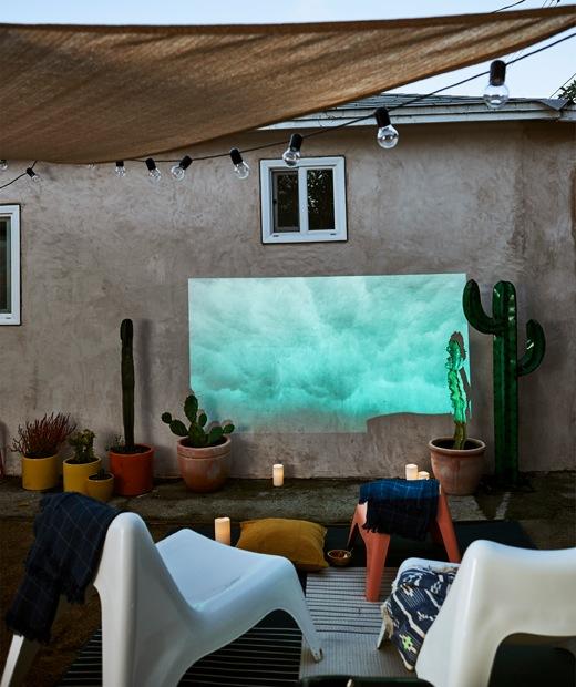 白色椅前方是投射在外牆上的電影,椅上有頂篷和裝飾燈串,旁邊則有蠟燭和盆栽。