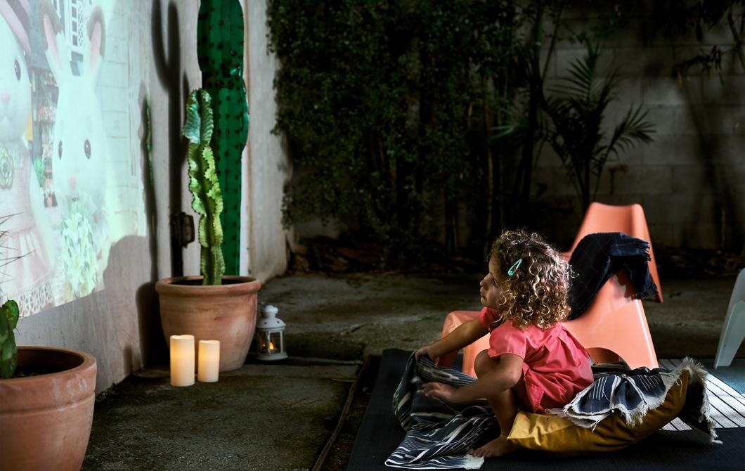 一名小孩坐在被和咕𠱸上,欣賞投映在外牆上的卡通片,旁邊有仙人掌盆栽和LED蠟燭。