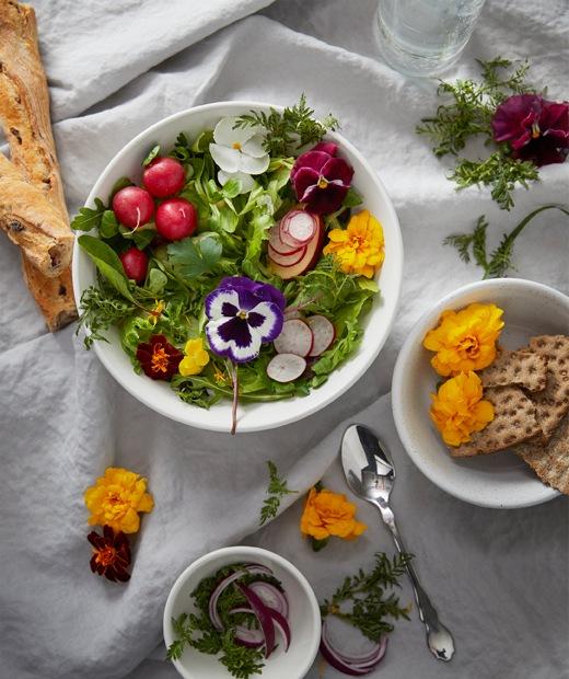 餐檯的一角放有白色的皺布,不同大小的碗放有麵包、自家種植蔬菜和花。
