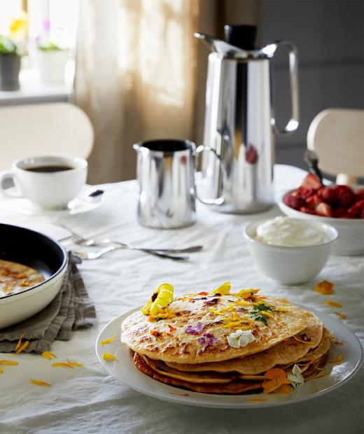 鋪上檯布的早餐檯,放有咖啡壺、士多啤梨和忌廉,以及用鮮花點綴的班戟。