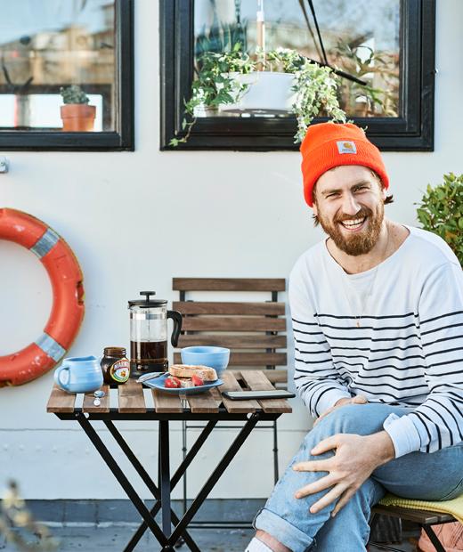 Gareth坐在船屋外的餐檯旁,檯上放有早餐。