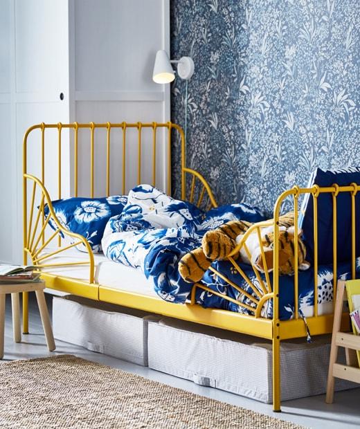 採用黃色床架的兒童床及藍色繪花圖案床上用品,床下有貯物箱,床邊設有壁燈。