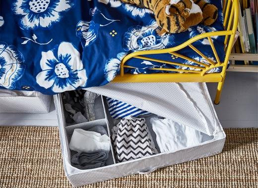 採用黃色床架的兒童床及藍色床上用品,床下有收納衣物的開放式貯物箱。