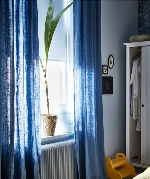 裝有白色捲軸簾及藍色窗戶,窗邊有一盆盆栽,旁邊的衣櫃打開。