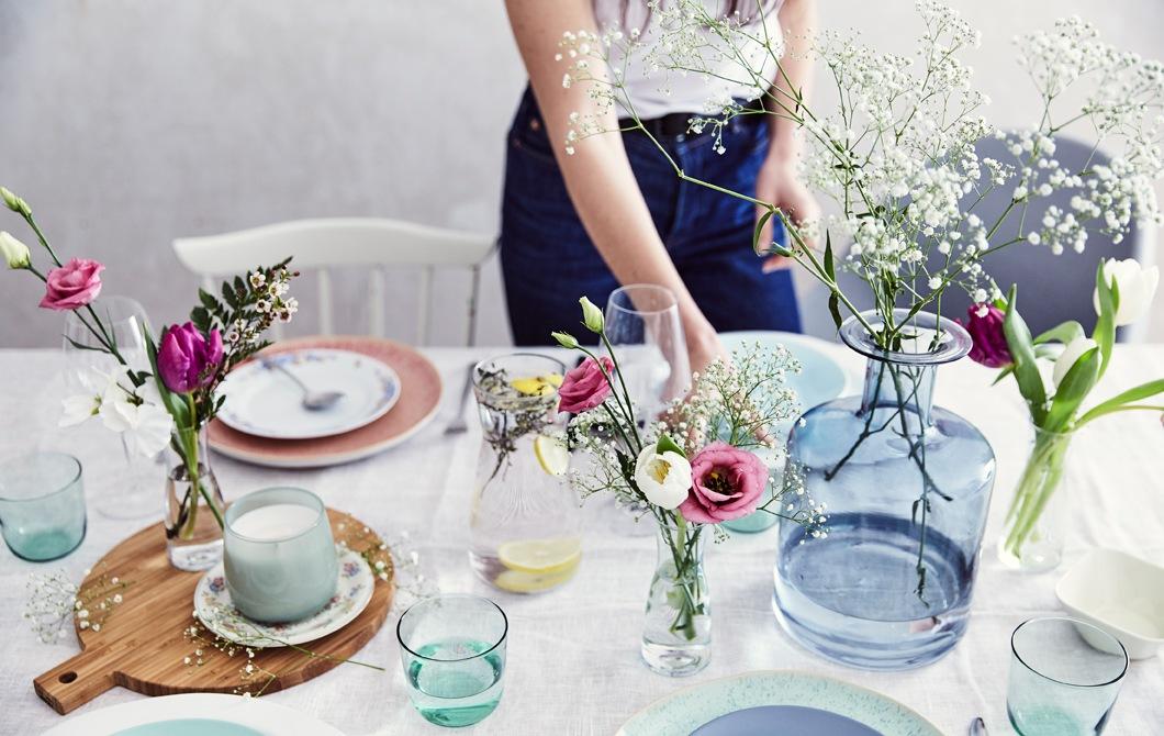 擺放粉色餐具的餐檯,檯上有以不同形狀及大小的玻璃花瓶盛載的鮮花,還有一塊木砧板及棉質檯布。