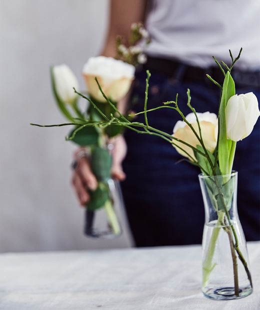 A person holding a vase of fresh flowers and another vase of flowers on a table in front.