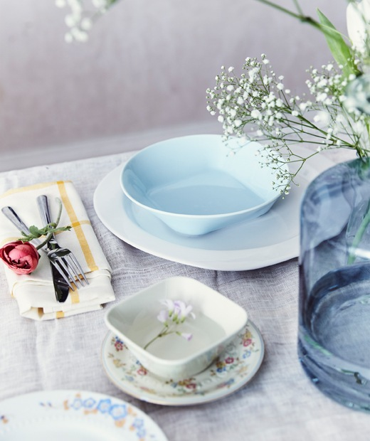 A place setting with a mix of pastel and patterned crockery and a large blue vase of flowers on a white table cloth.