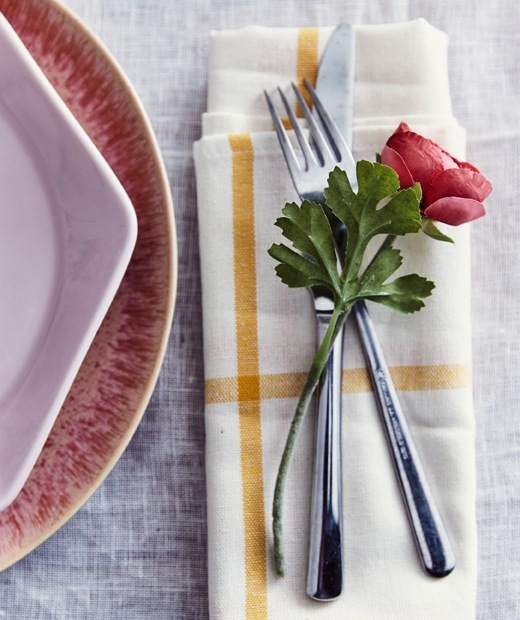 An artifical flower resting on a knife and fork on a yellow and white patterned napkin, next to pink plates.