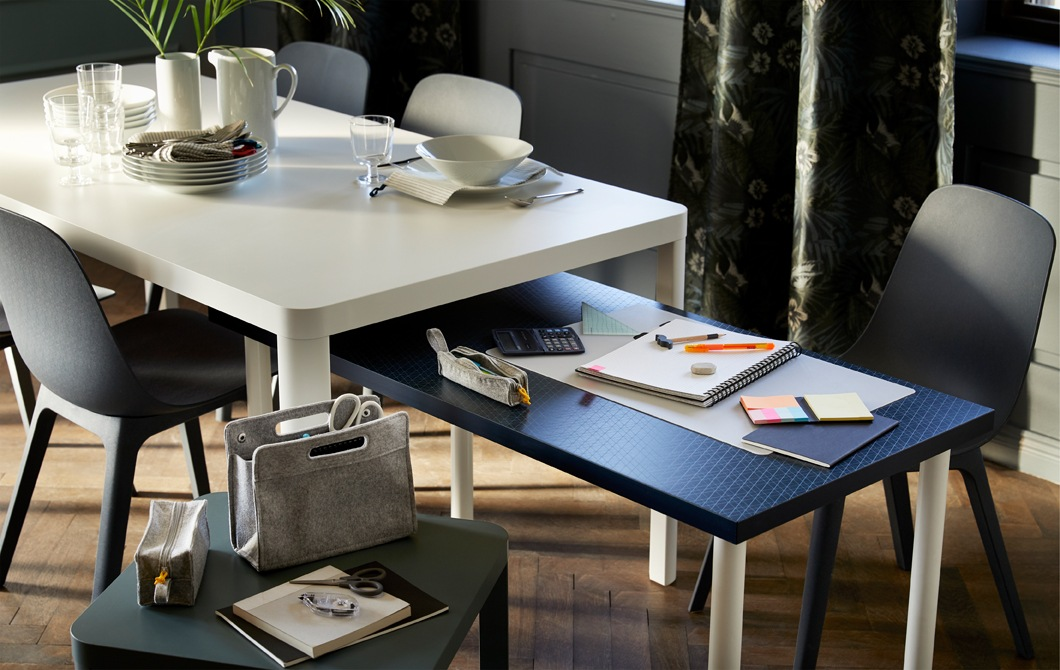 Like full-size nest tables, a lower table with schoolwork comes out from under a dinner table with tableware about to be set.