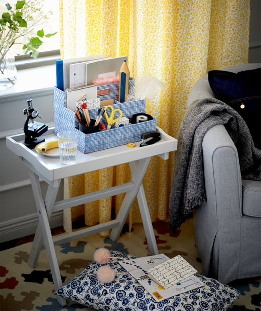 Standing between an armchair and window in a living room, a tray table is decked out for studying, including drink and fruit.