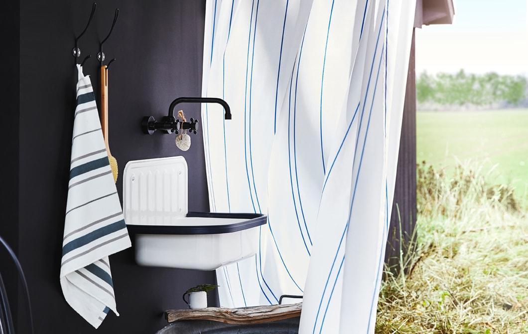 黑色牆上有毛巾、掛鈎、星盆及水龍頭,條紋浴簾後有一片草地。