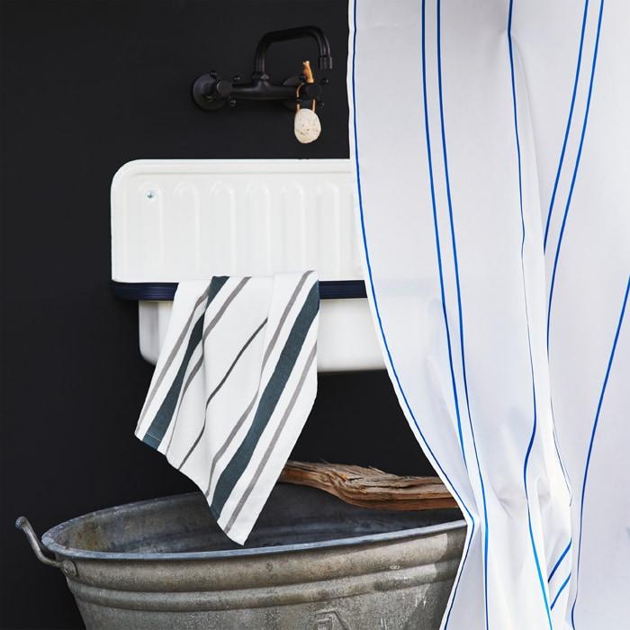 白色星盆配黑色水龍頭,還有條紋毛巾及浴簾,下面則有個金屬水桶。