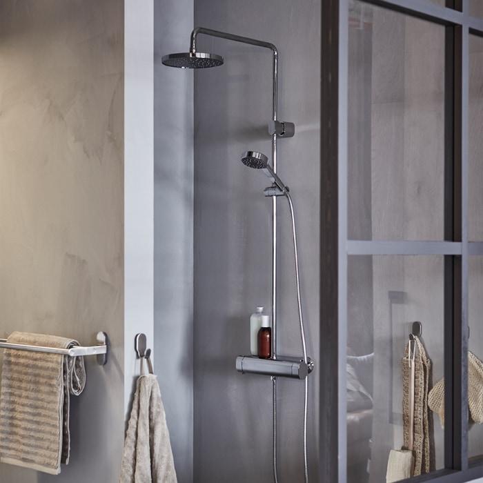 設有淋浴龍頭及花灑的灰色淋浴間,掛鈎上掛有米色毛巾。