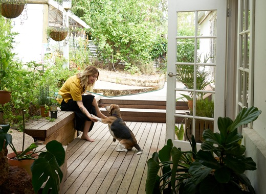 Nici與小狗坐在白色門外花園木平台上。