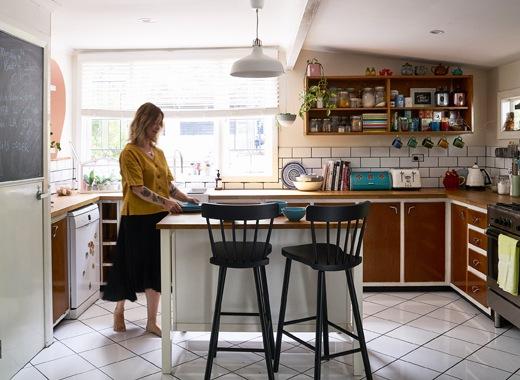 Nici站在島形工作檯旁,旁邊有兩張黑色吧檯凳,廚房設有啡色廚櫃、層架和一個大窗。