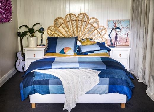 睡房內有編織柳枝床頭板、藍色寢具和白色床頭几。