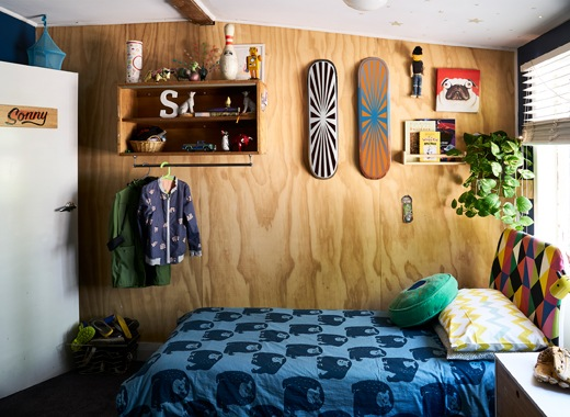 兒童睡房的木牆裝有層板和滑板,房內還有藍色圖案寢具。