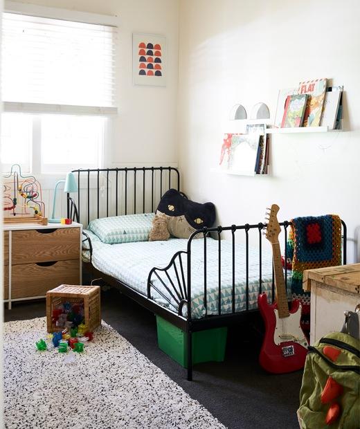 兒童睡房內有白牆、黑色床架,層板上有書本。