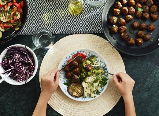 有個人拿著刀叉享用食物,檯上擺放多碟蔬菜及素菜丸。