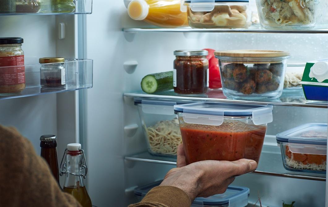 打開的雪櫃,內裡的層架上放滿裝著食物的透明食物盒。