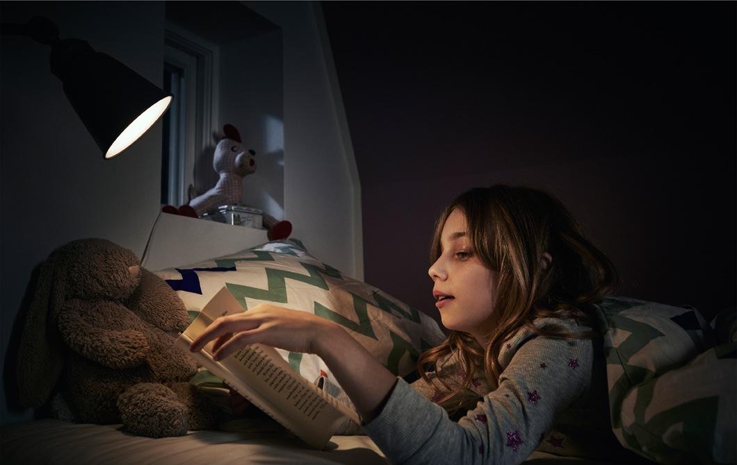 在床上看書的孩子,床邊有盞閱讀燈。