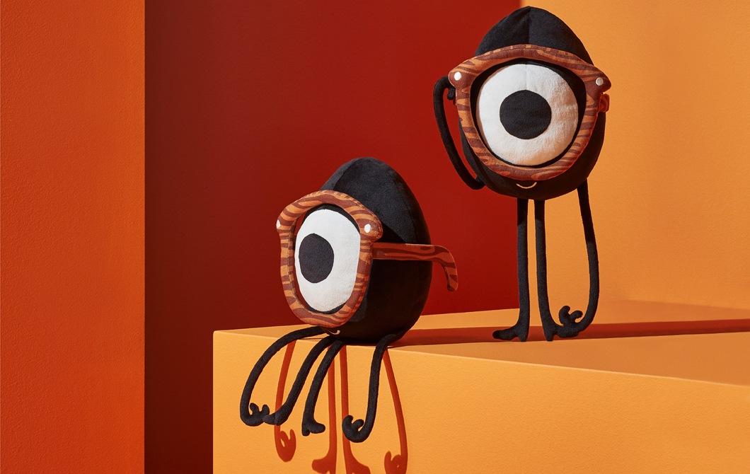 兩隻戴上單框眼鏡的獨眼蛋形毛公仔,配以橙色和紅色背景。