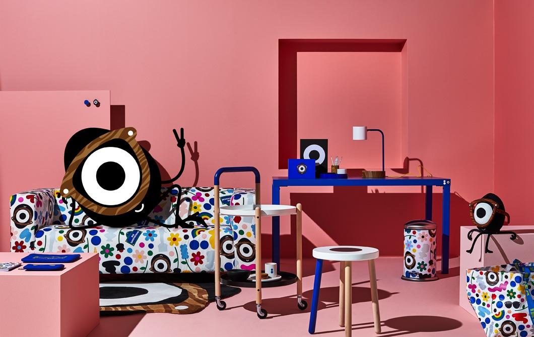 粉紅色房間內的藍色書檯、角几及凳,有個卡通人物靠在奪目的圖案梳化上。
