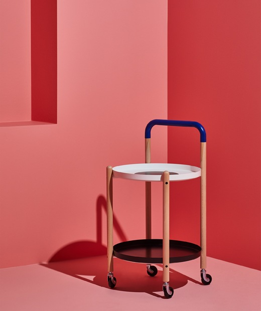 設有滾輪和木框架的角几,下面設有層架,放在粉紅色房間內。