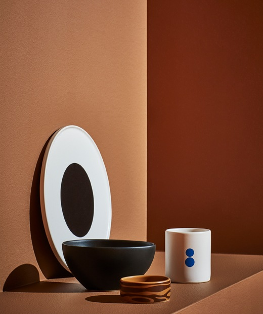 黑心白色碟、黑色大碗、啡色細碗及白色杯,全部放在橙色梯級上。