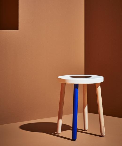 由一隻藍色腳及白色檯面組成的木凳,放在橙色房間內。
