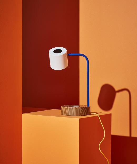書檯燈連啡色燈座、藍色燈臂及白色燈罩,放在橙色梯級上。