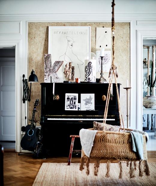 採用木地板的房間放有黑色鋼琴和藤製吊椅。