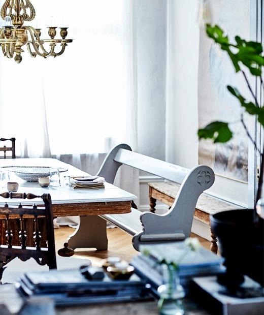 餐檯旁放有一張白色木長凳,上方有盞金色吊燈。
