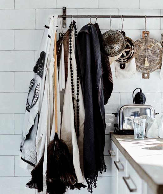 布料、抹布和篩掛在白色瓷磚牆上的金屬掛桿上。